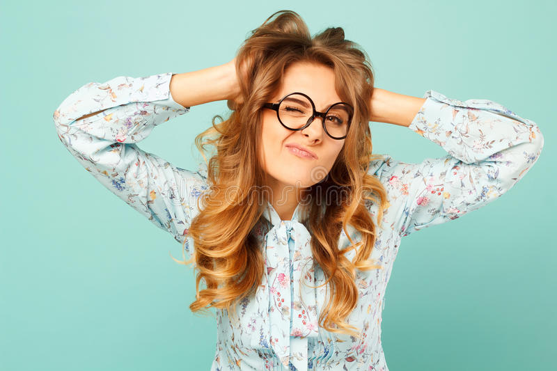 Portrait of a beautiful young student wearing glasses and showing funny emotions on face over blue background. Portrait of a beautiful young student wearing stock photography