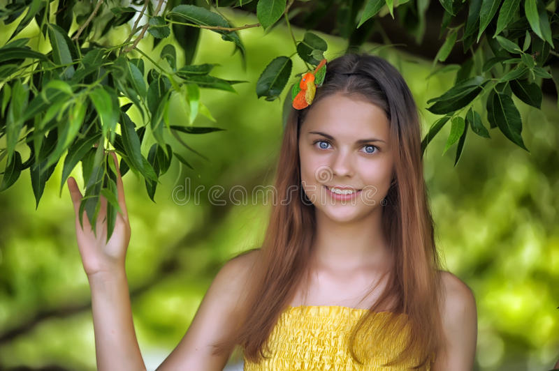 Portrait of a beautiful young teenager girl. Near a tree in summer stock photography