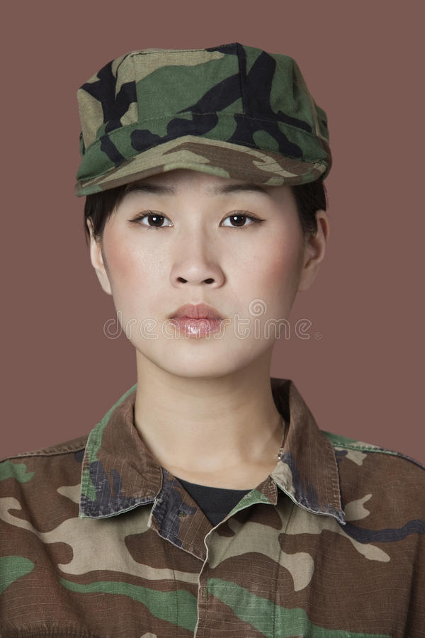 Portrait of beautiful young US Marine Corps soldier in camouflage clothing over brown background royalty free stock images