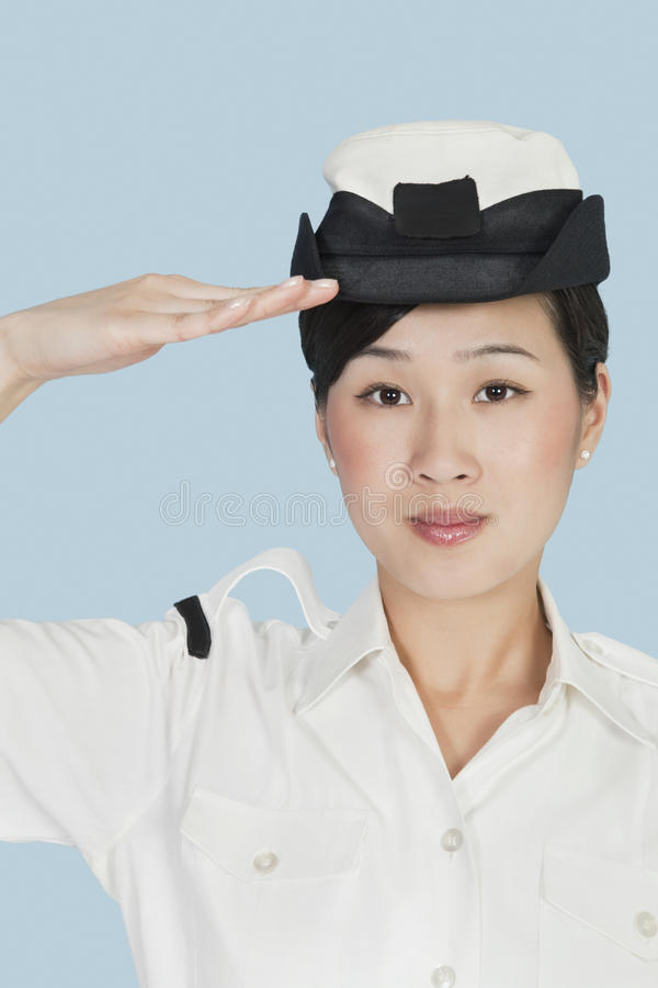 Portrait of a beautiful young US Navy officer saluting over light blue background stock photography