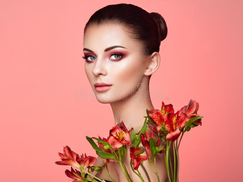 Portrait of beautiful young woman with Alstroemeria flowers. Brunette woman with luxury makeup. Perfect skin. Eyelashes. Cosmetic eyeshadow. Red flowers. Coral stock images