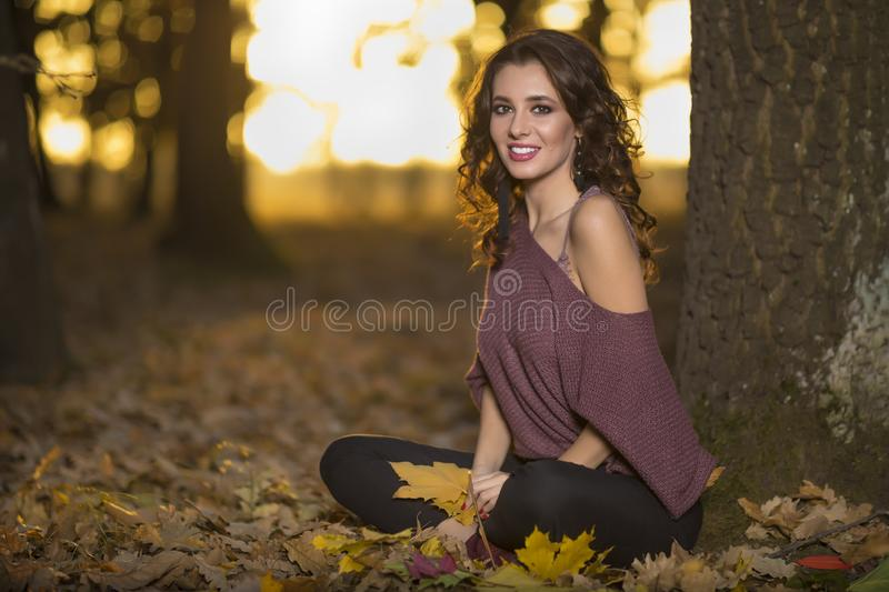 A portrait of a beautiful young woman in an autumn forest. Lifestyle, autumn fashion, beauty. royalty free stock image