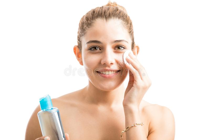 Happy woman taking care of her skin. Portrait of a beautiful young woman with bare shoulders removing her makeup and taking care of her skin royalty free stock image