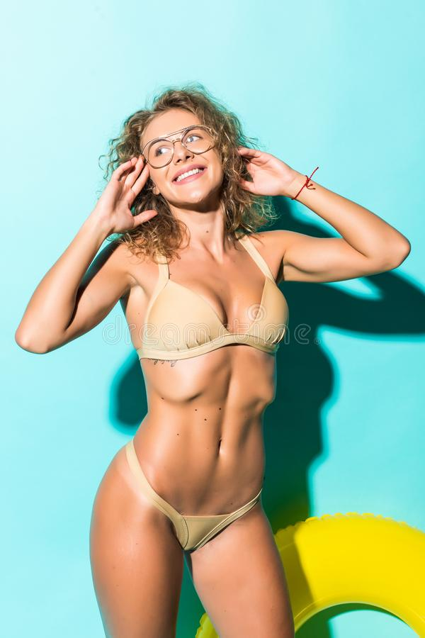 Portrait of beautiful young woman in bikini and glasses playing with inflatable yellow float isolated on blue background. Portrait of beautiful young woman in royalty free stock photo