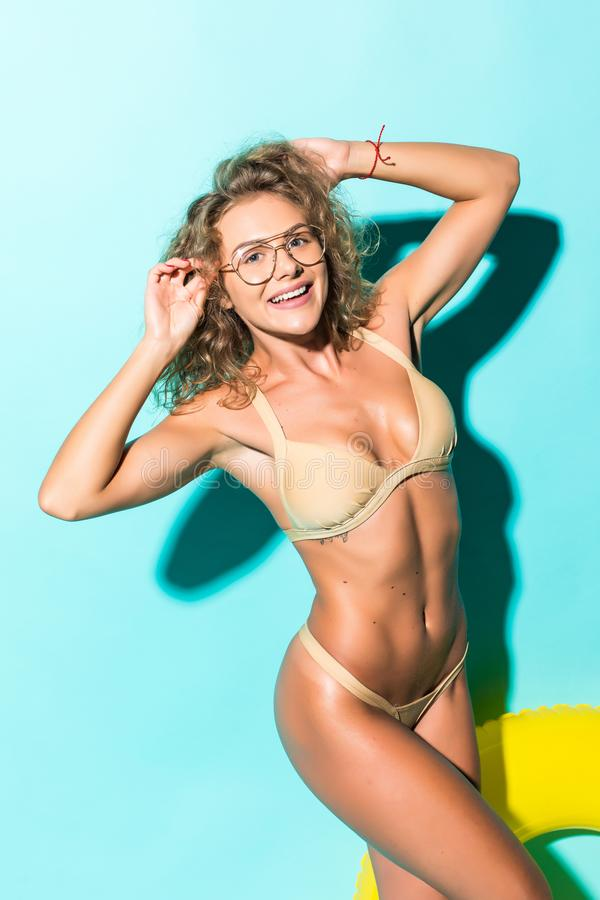 Portrait of beautiful young woman in bikini and glasses playing with inflatable yellow float isolated on blue background. Portrait of beautiful young woman in stock images