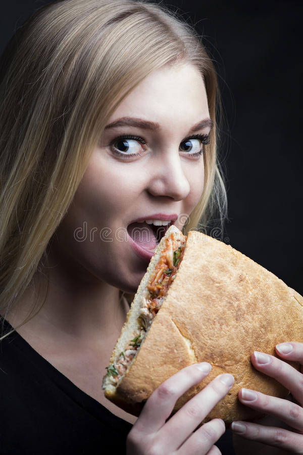 Portrait of a beautiful young woman biting a sandwich royalty free stock image