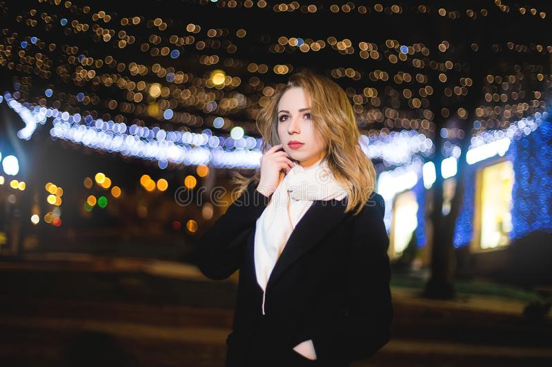 Portrait of Beautiful young woman in black on a background of a night city stock images