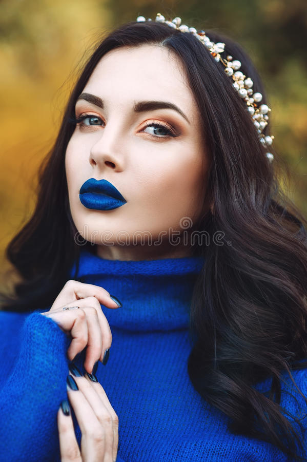 Portrait of beautiful young woman with blue lips and blue sweater with accessory on her head in the park stock photos