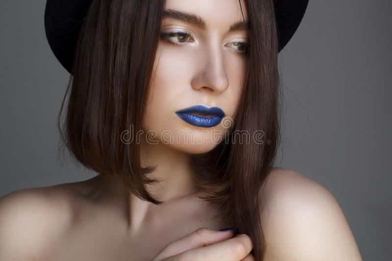 Portrait of beautiful young woman with blue lips and in hat. Beauty concept. stock photo