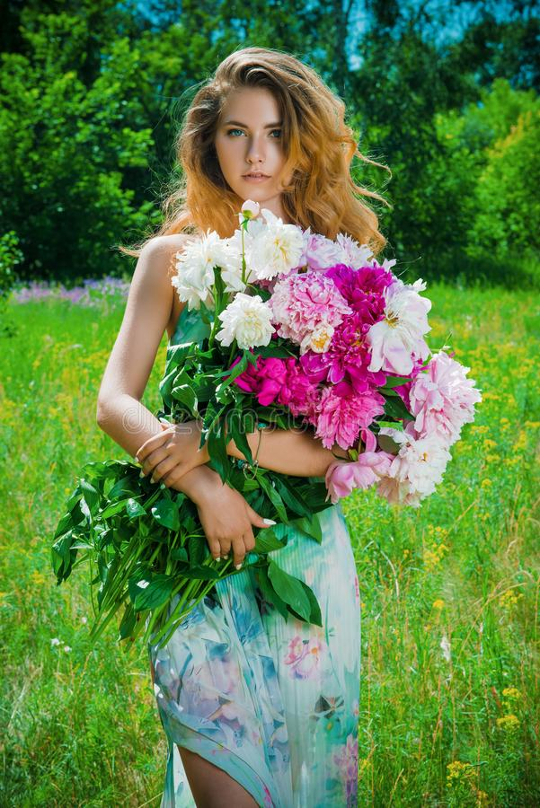 Lady with summer flowers. Portrait of a beautiful young woman with a bouquet of fresh summer flowers outdoor. Beauty, cosmetics. Summer vacation stock images