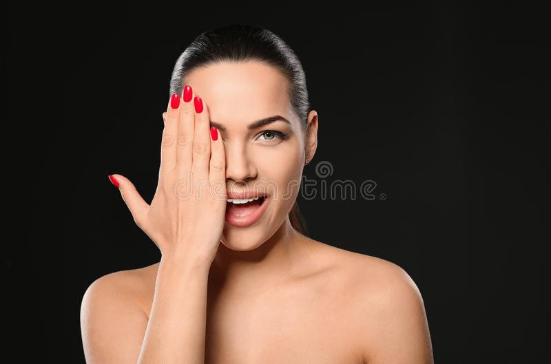 Portrait of beautiful young woman with bright manicure on black. Nail polish trends stock photo