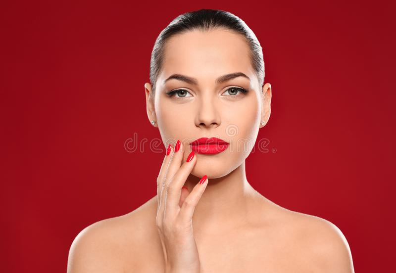 Portrait of beautiful young woman with bright manicure on color background stock photography