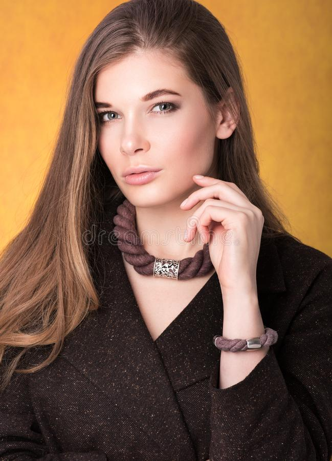 Portrait of beautiful young woman in a brown cloak with a necklace around his neck and a bracelet on her arm royalty free stock photos
