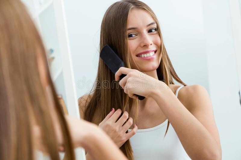 Beautiful young woman brushing her long hair in front of her mirror. Portrait of beautiful young woman brushing her long hair in front of her mirror royalty free stock photos