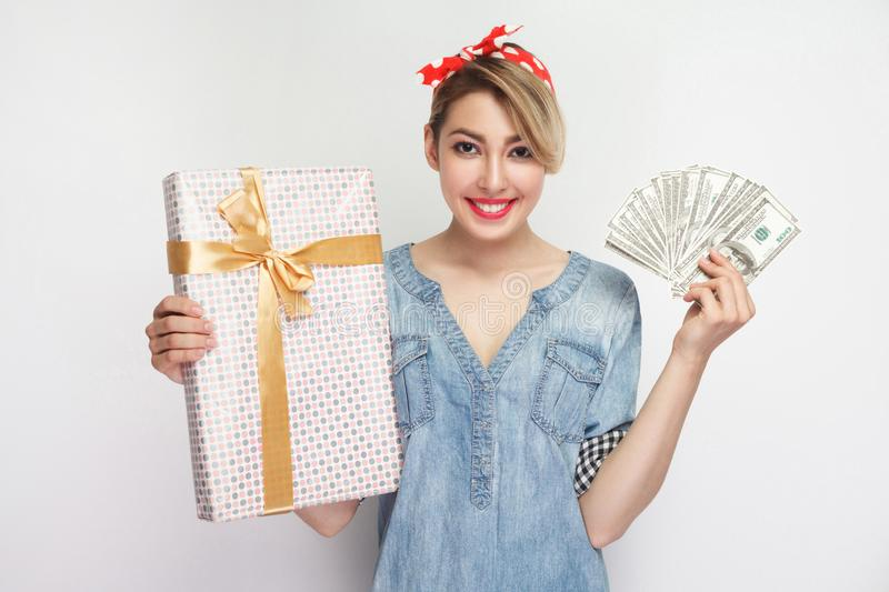 Portrait of beautiful young woman in casual blue denim shirt with makeup and red headband standing, showing gift box and fan stock image