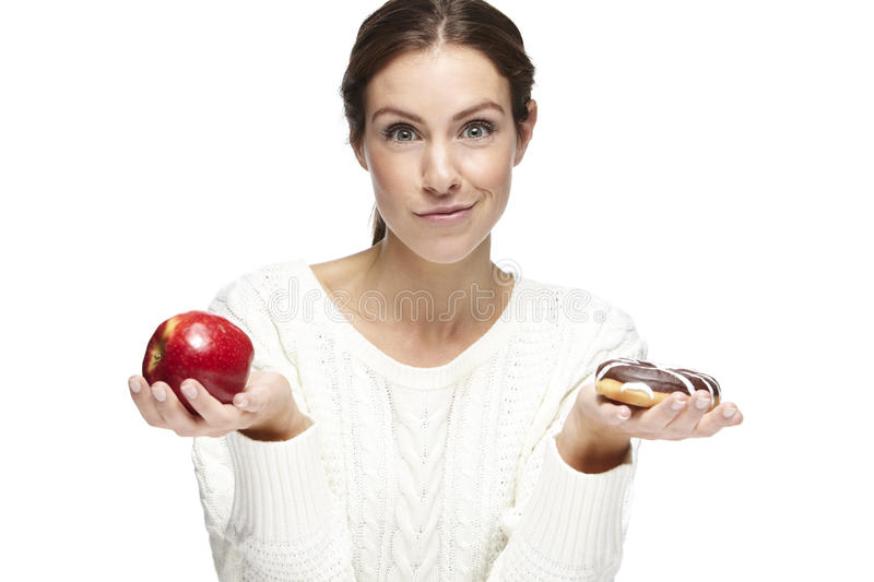 Portrait of a beautiful young woman, choosing between apple and donut royalty free stock photos
