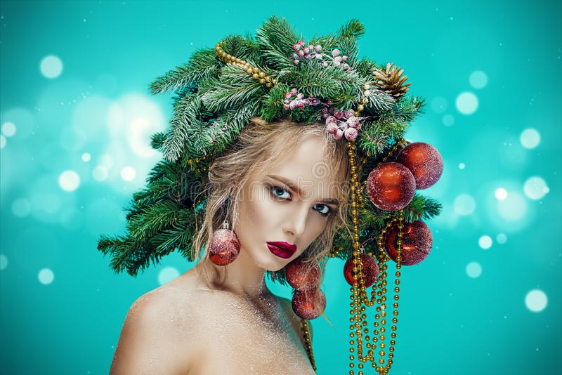 Woman with christmas tree. Portrait of a beautiful young woman with christmas tree in hairstyle decorated with beads and balls over blue background. Holiday make royalty free stock photos