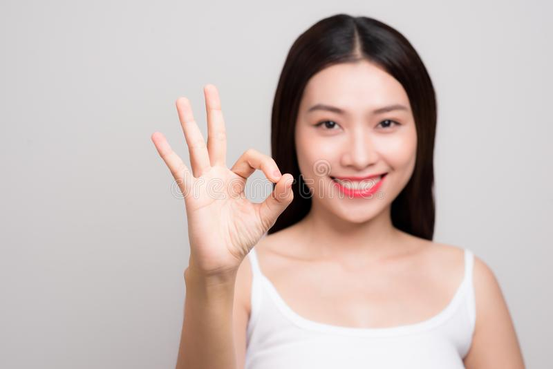 Portrait of a beautiful young woman with clean skin gesture ok s royalty free stock photos