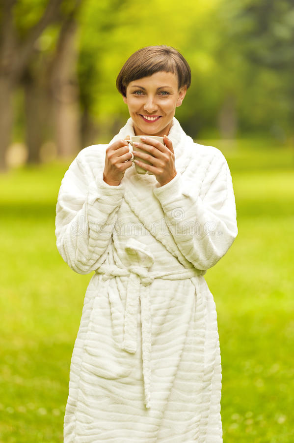 Portrait of beautiful young woman with coffee cup standing in ga stock image
