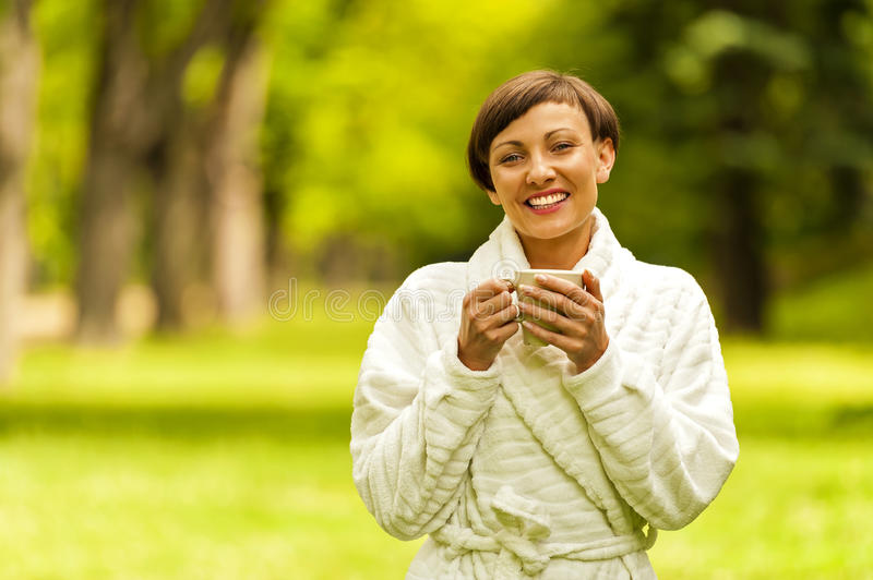 Portrait of beautiful young woman with coffee cup standing. stock photo