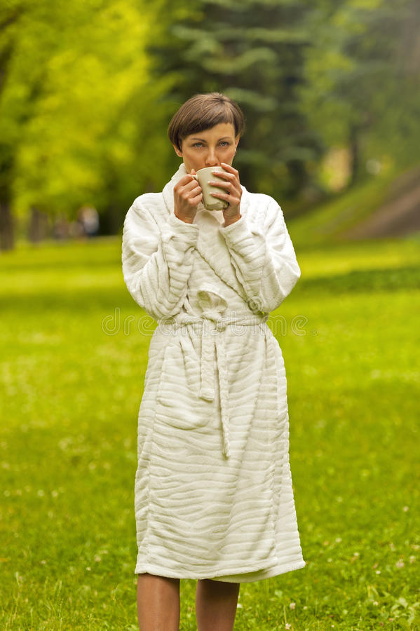 Portrait of beautiful young woman with coffee cup standing. stock photos