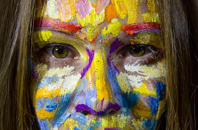 Portrait of beautiful young woman with oil painting on the face stock photo