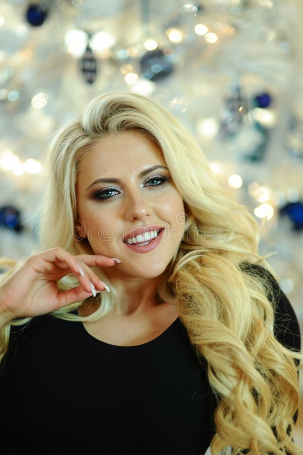 Portrait of beautiful young woman with curly blond hair and glamor makeup. Fashion indoor shot with Christmas tree on the background stock photo