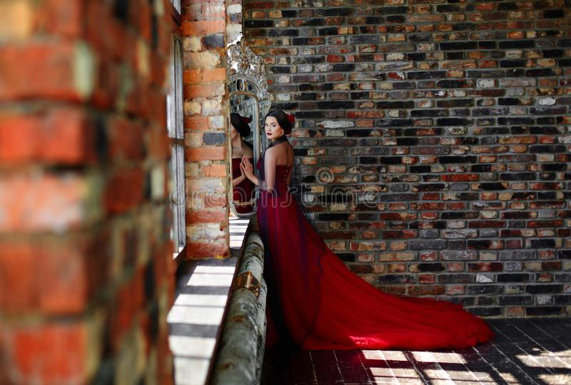 Portrait of a beautiful young woman dancer in a red dress near the window. Portrait of a beautiful young woman dancer in a red dress near the window stock photos