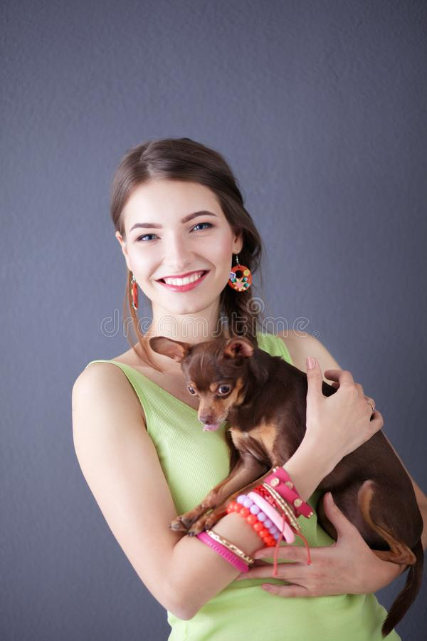Portrait of the beautiful young woman with dog on the grey background royalty free stock photography