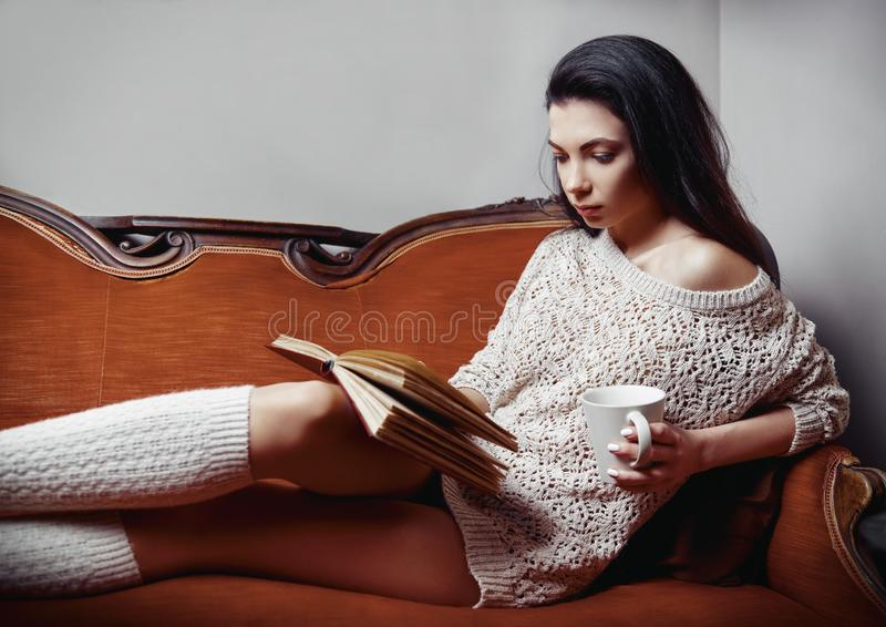 Portrait of beautiful young woman dressed in sweater and knee socks. Alluring girl with cup in hand lying on sofa and reading book stock photography