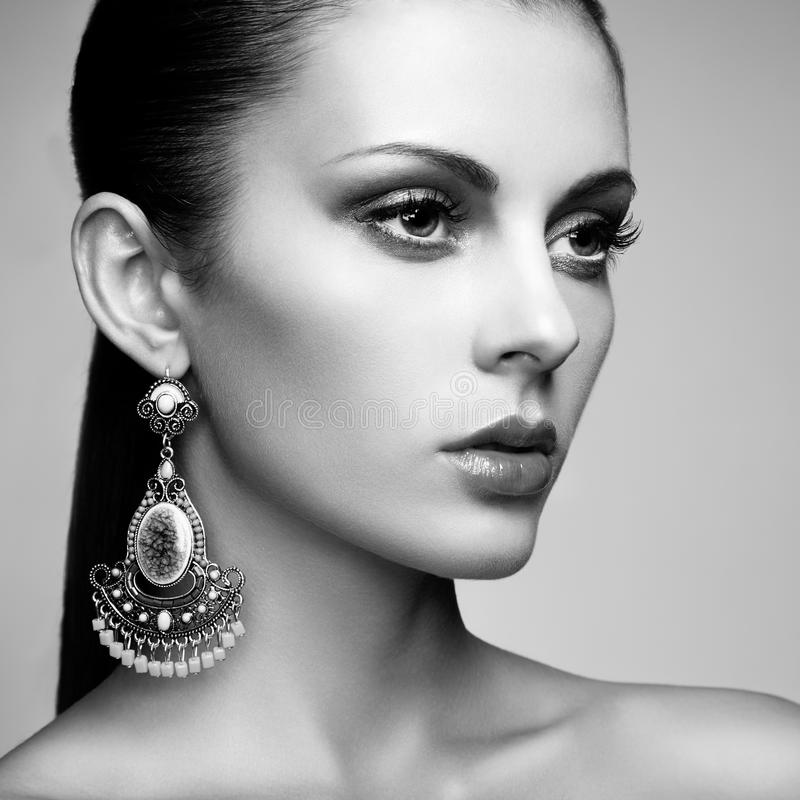 Portrait of beautiful young woman with earring. Jewelry and accessories. Perfect makeup. Fashion photo stock photos