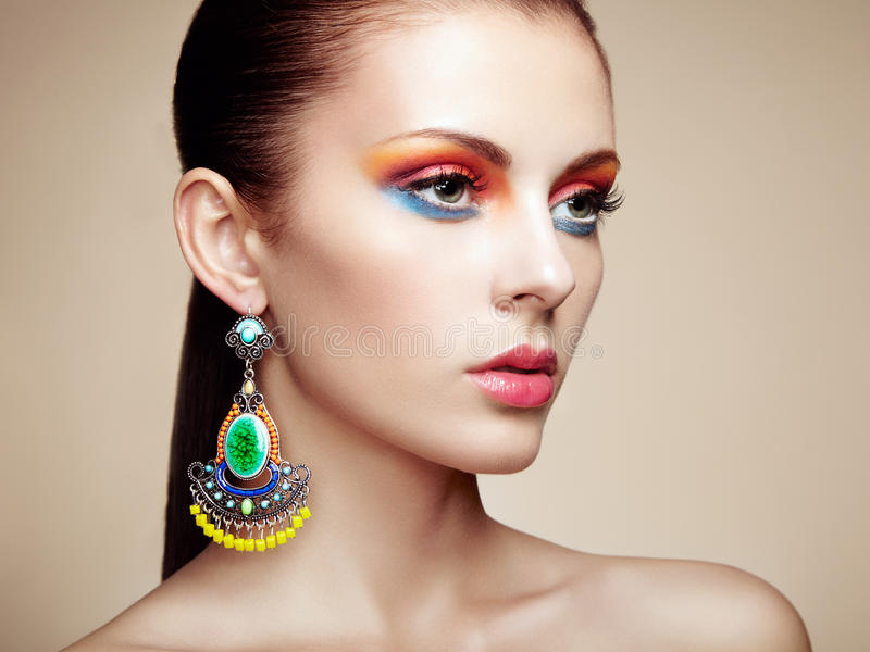 Portrait of beautiful young woman with earring. Jewelry and accessories. Perfect makeup. Fashion photo stock photography