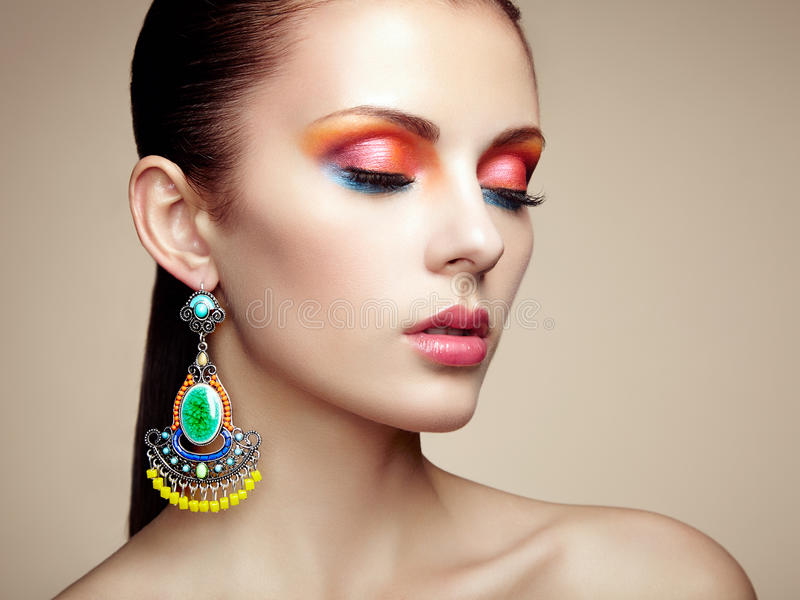 Portrait of beautiful young woman with earring. Jewelry and accessories royalty free stock images