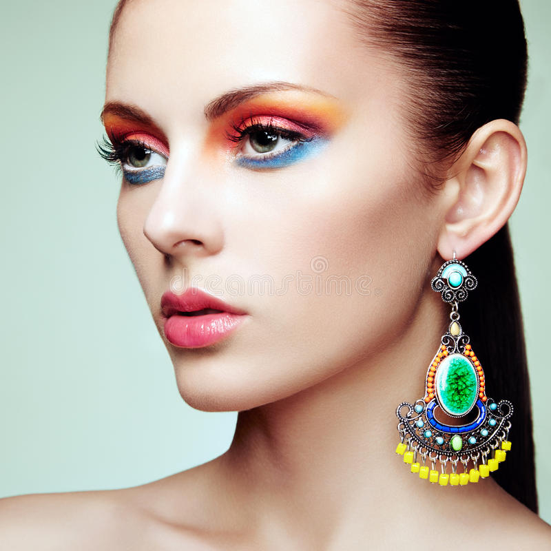 Portrait of beautiful young woman with earring. Jewelry and accessories. Perfect makeup. Fashion photo royalty free stock photography