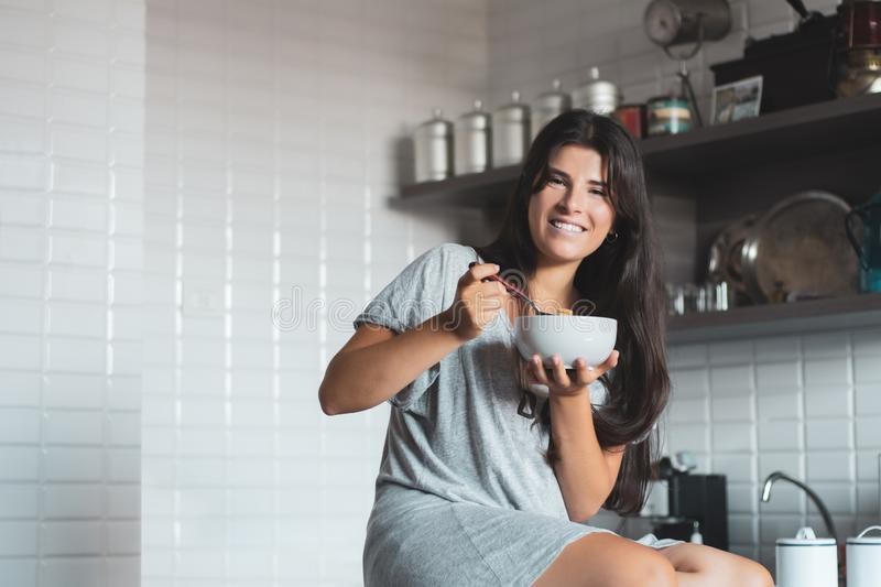 Young woman having breakfast in the kitchen royalty free stock photography