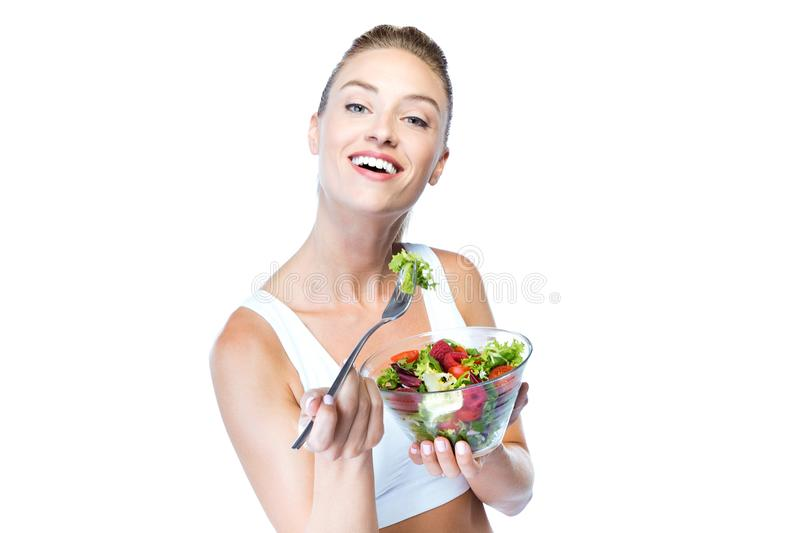 Beautiful young woman eating salad over white background. Portrait of beautiful young woman eating salad over white background stock photography