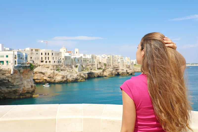 Portrait of beautiful young woman enjoying Polignano a mare view, Mediterranean Sea, Italy royalty free stock photo