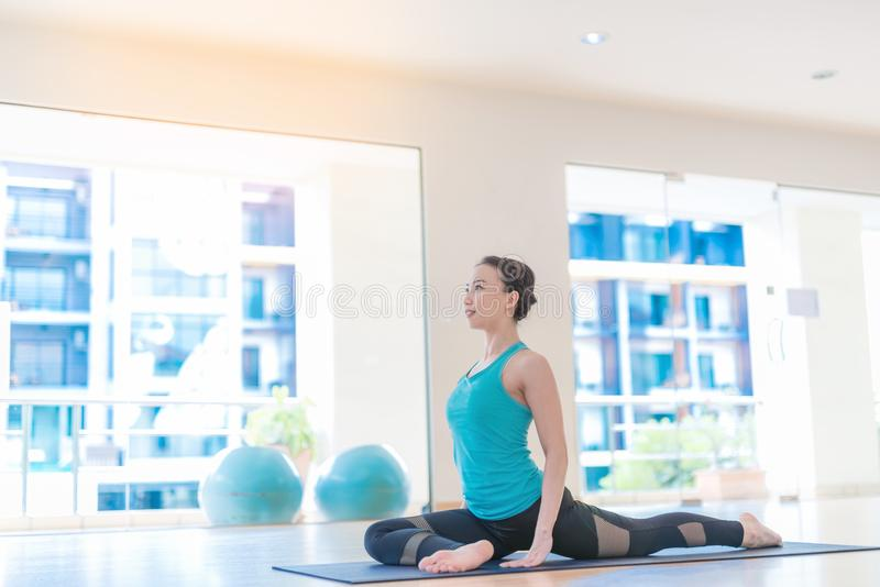 Asian woman Doing Yoga In yoga studio royalty free stock photography