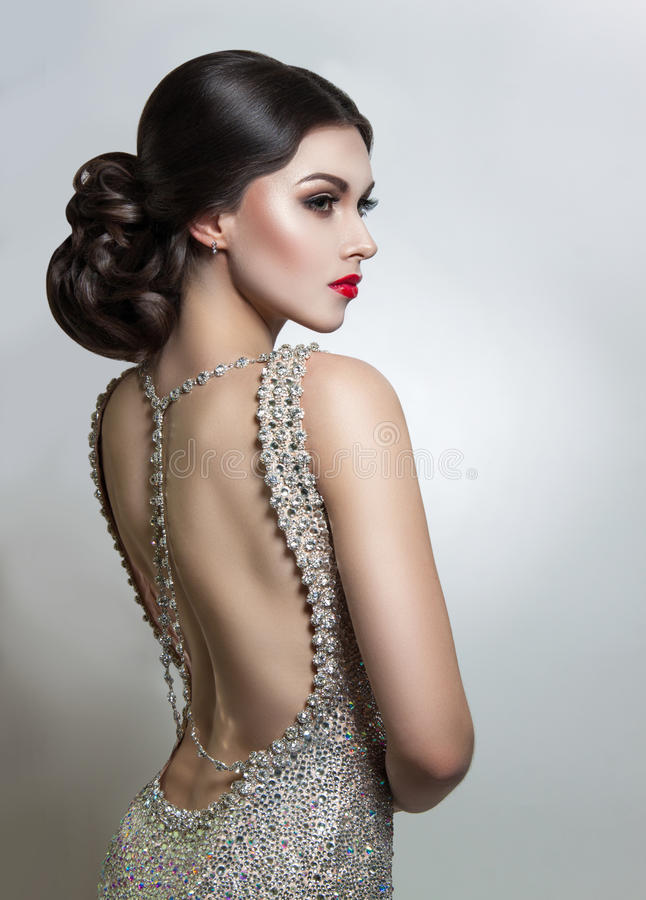 Portrait Beautiful young woman in an evening dress crystal. Perfect beauty, red lips, bright makeup. royalty free stock photography