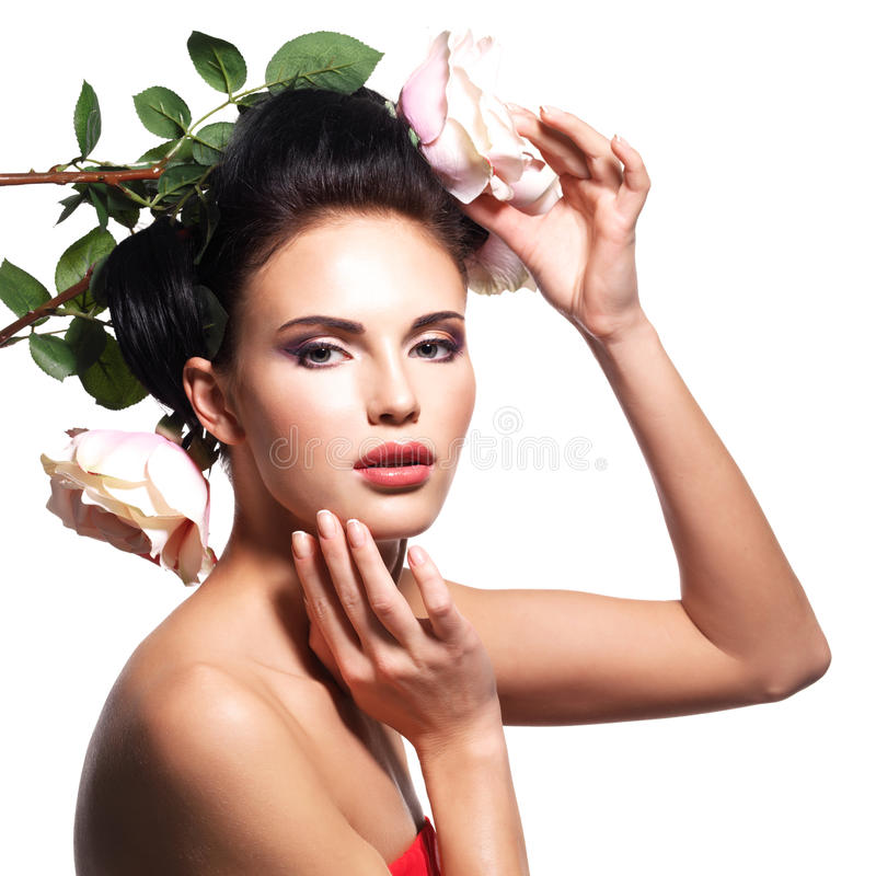 Portrait of beautiful young woman with flowers in hair. Portrait of beautiful young woman with flowers in hair touching her face - isolated on white royalty free stock images