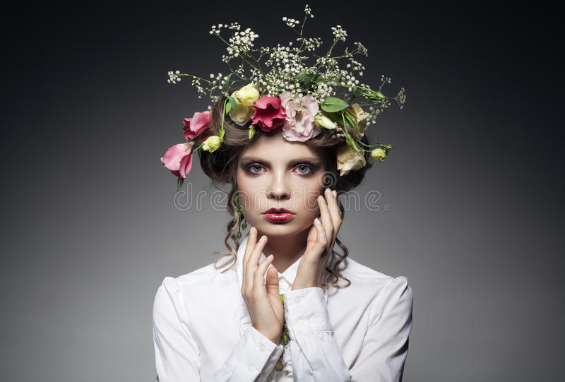 Portrait of beautiful young woman with flowers in hair. On dark background with copyspace stock photography