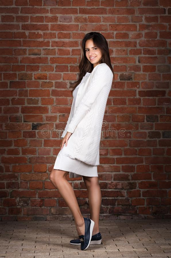 Portrait of beautiful young woman in full growth. Casual wear, long white sweater royalty free stock images