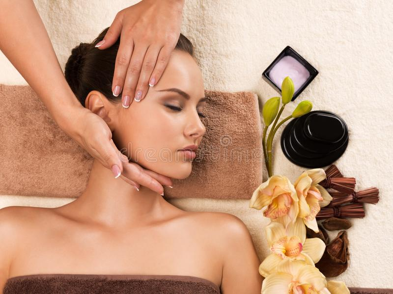 Beautiful woman getting head massage in the spa salon. Portrait of beautiful young woman getting head massage in the spa salon. Beauty treatment concept stock images