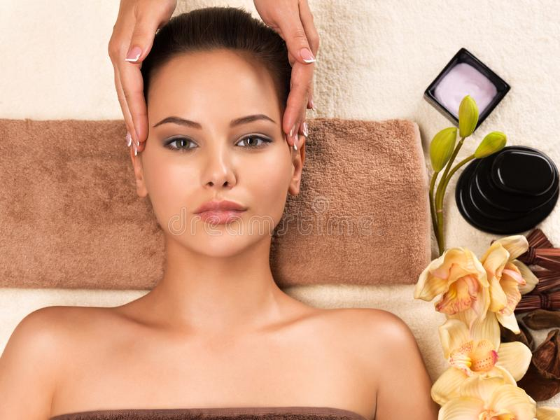 Beautiful woman getting head massage in the spa salon. Portrait of beautiful young woman getting head massage in the spa salon. Beauty treatment concept royalty free stock photos
