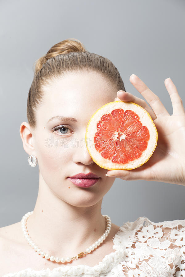 Portrait of Beautiful young woman with grapefruit in her hand stock photo