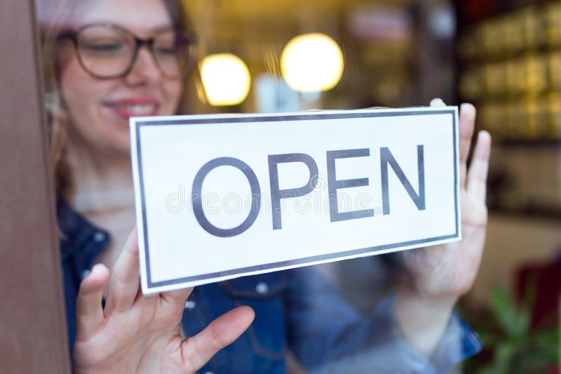 Beautiful young woman hanging the open sign in the store. stock photos