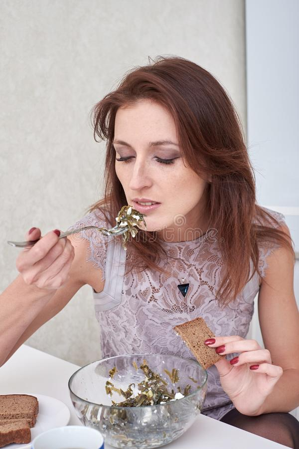 Portrait of beautiful young woman having healthy breakfast in the kitchen. stock photo
