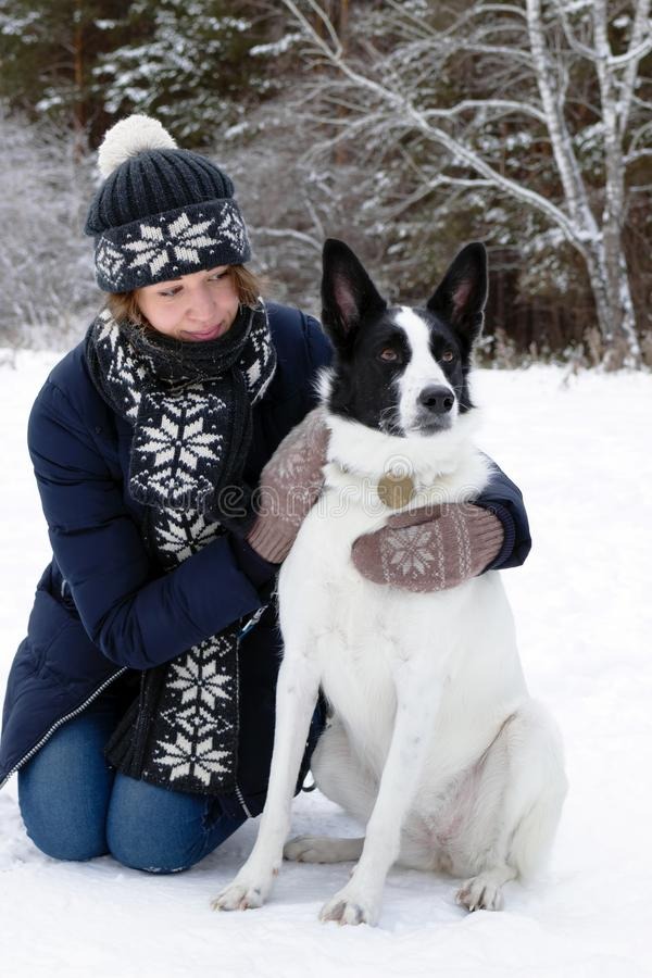 Portrait of beautiful young woman with her black and white dog on a background of winter snowy forest stock image