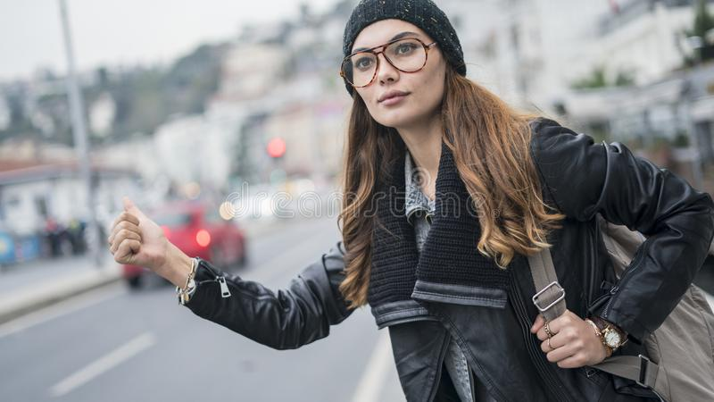 Portrait of a beautiful young woman hitchhiking on the road royalty free stock images