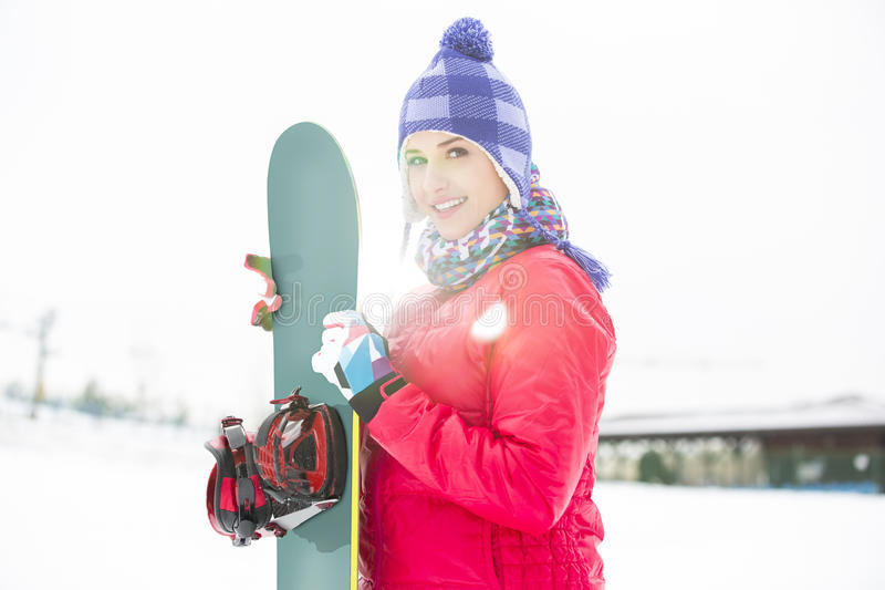 Portrait of beautiful young woman holding snowboard in snow royalty free stock image
